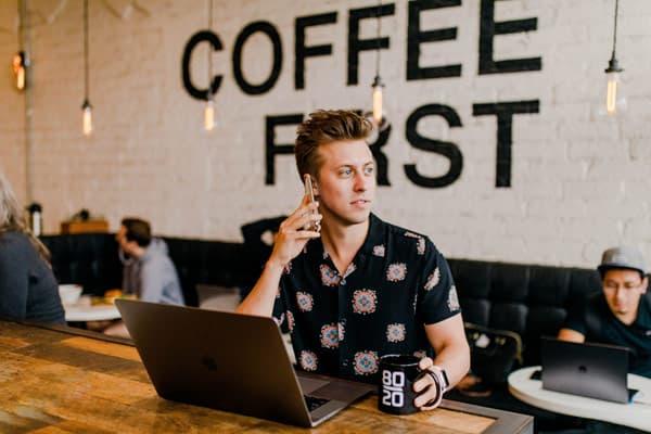 Junger Mann im Kaffee verdient Geld mit Social-Media